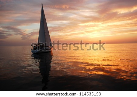 sailing boat in the sun set - stock photo