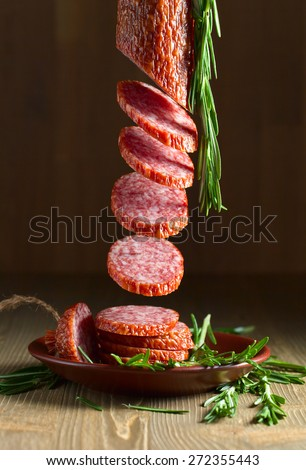 salami with rosemary on a old wooden table - stock photo