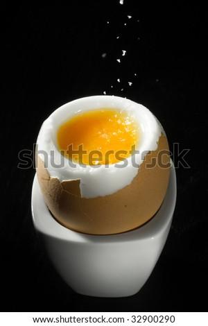 salt being sprinkled on softly boiled egg - stock photo