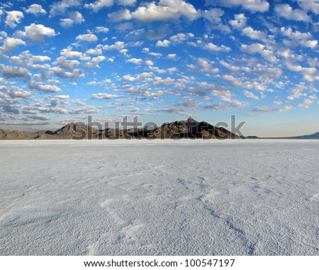 Salt Flats in foreground,mountains background, and a blue sky with hundreds of small puffy clouds./  Bonneville Salt Flats #4 / Natures beauty and a hot rodders dream. - stock photo