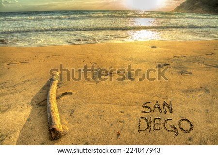 """san diego"" written on a golden shore at sunset - stock photo"
