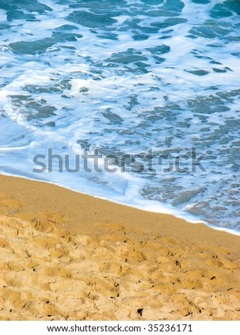 sand on a beach of Mediterranean sea and a turquoise wave - stock photo