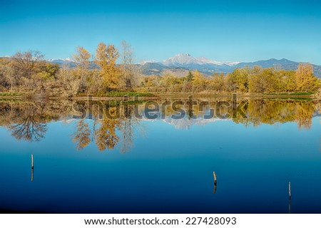 Scenic autumn season view of the twin Peaks, Mt meeker 13,911 ft and Longs Peak  14,256 ft  with mirror like reflections from Golden Ponds in Longmont Colorado, Boulder County. - stock photo