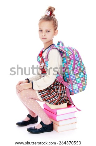 Schoolgirl with a backpack sitting on the books- isolated on white background - stock photo