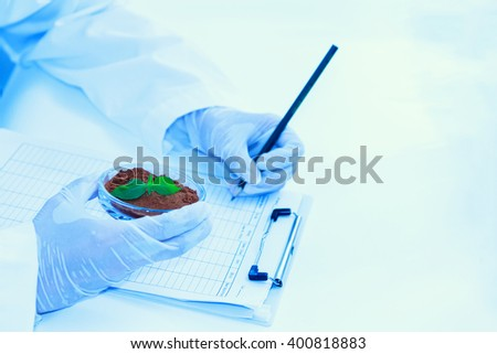 (SCIENCE) Scientist holding test tube or some equipment of science with hand in laboratory, her choos test tube for make or test something about science experience, science content, Film effect. - stock photo