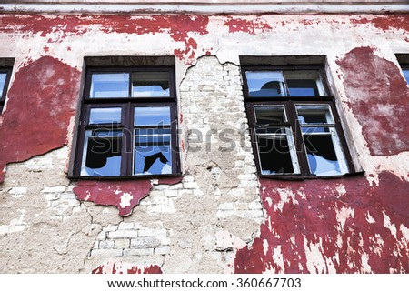 score windows with broken windows in an abandoned building crumbling - stock photo