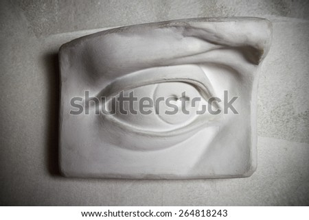 Sculpture of eye on the grey wall. - stock photo