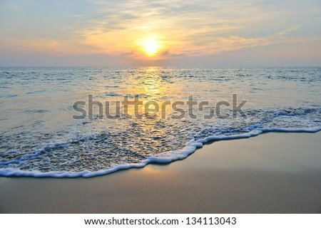 sea wave on the beach at sunset time - stock photo