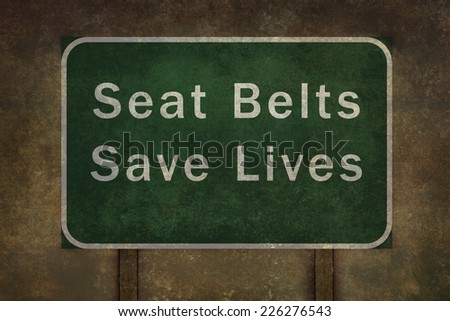 """Seat belts save lives"" roadside sign illustration, with distressed ominous background - stock photo"