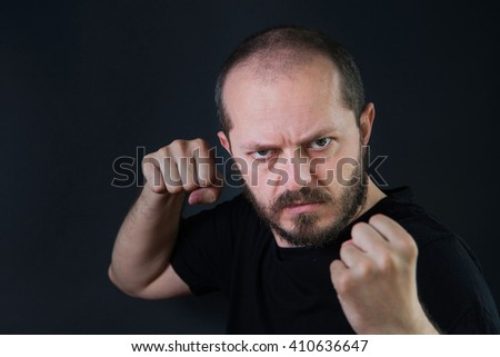 Serious aggressive man with beard and mustaches on black background in low key, holding fists and threatening, ready for fight  - stock photo