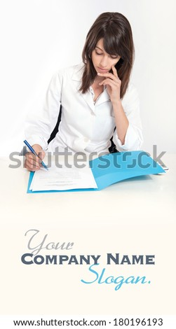 Serious young woman in a lab coat sitting at the desk  with an open folder  - stock photo