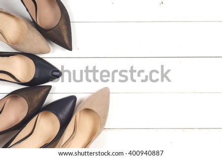Set of different shoes, Shot of several types of shoes, Several designs of  women shoes. Leather Shoe, Sport Shoe. Pile of various female shoes on wooden background - stock photo