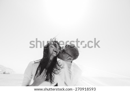 sexy couple young beautiful girl and the man in sunglasses and white clothes on their honeymoon in Cyprus on the beach - stock photo