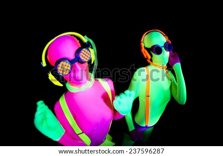 2 sexy female disco dancer poses in UV costume - stock photo