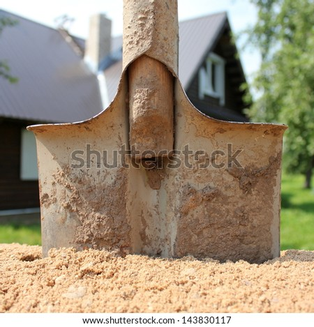 Shovel and sand pile against the house - stock photo