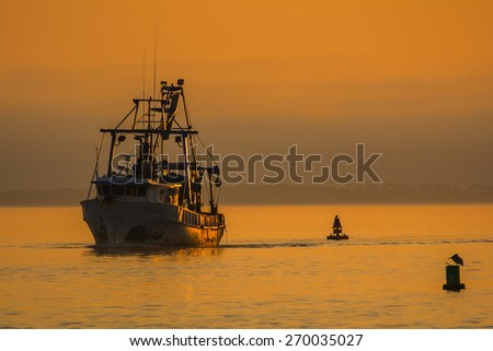 Shrimping boat at sunset in Florida.   Vintage fishing boat coming in from a day on the water.  - stock photo