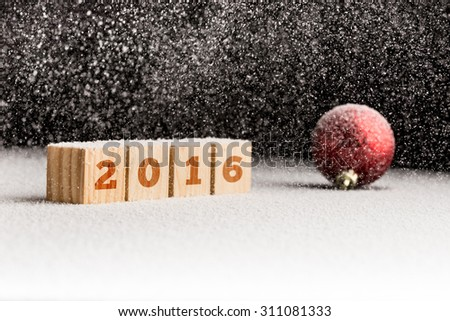 2016 sign on wooden cubes and red christmas ball lying on a snowy surface with gentle snowflakes falling from above. Copy space ready for your text. - stock photo