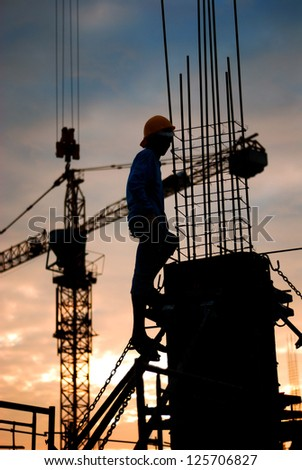 silhouette of constructionworker on constructionsite - stock photo