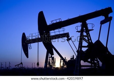 Silhouette of oil pump jacks with sunrise. - stock photo