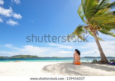 Single young bikini girl sits in the shadow of a coconut tree on white beach , with clean background of beautiful blue sky and cloudscape and. Shot on Pass Island, Coron, Palawan, Philippines - stock photo