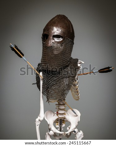 Skeleton of the dead warrior in the helmet and chain armour with arrows in his body - stock photo