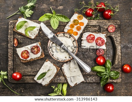 slice of fresh rye bread with cream cheese with basil and tomatoes on vintage wooden cutting board, viewed from above - stock photo