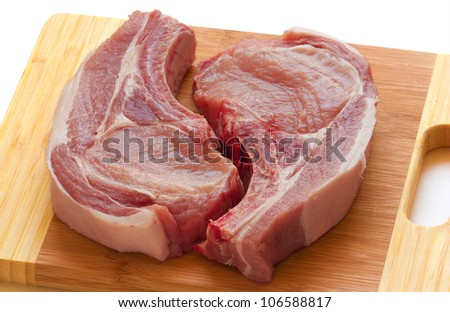 2 slices of fresh pork meat with a bone on a wooden cutting board, isolated - stock photo
