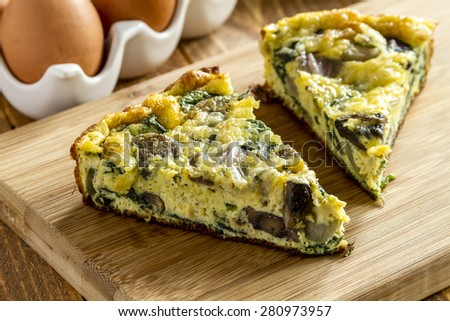 2 slices of spinach mushroom and egg frittata sitting on wooden cutting board - stock photo