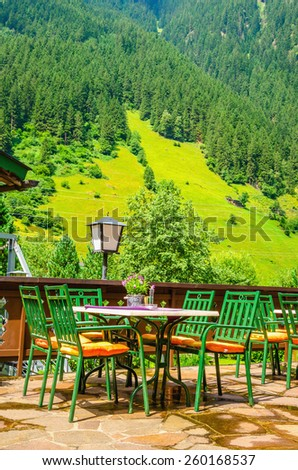 Small Alpine restaurant on the terrace on the background of the Alps, Austria - stock photo