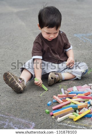 Small child, boy or girl, drawing on a asphalt road or pavement with a chalk. - stock photo