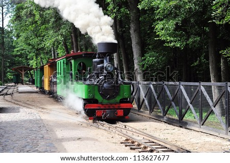 small green old steam locomotive rides on rails - stock photo