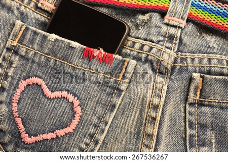smart phone in the pocket of jeans - stock photo