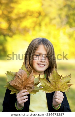 smiling child with autumn leaves - stock photo