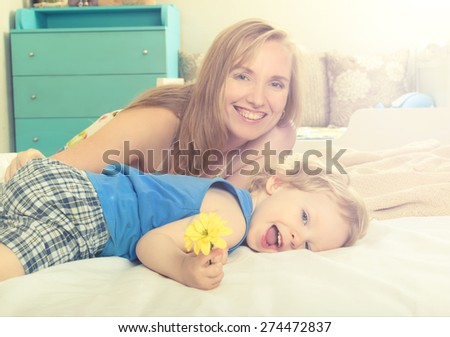 Smiling embracing mom with her baby lying in bed - stock photo