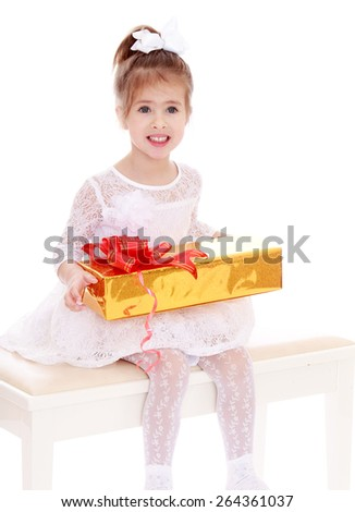 Smiling girl in a beautiful white dress with a gift - isolated on white background - stock photo