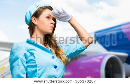 Smiling hostess with airplane on the background  - stock photo