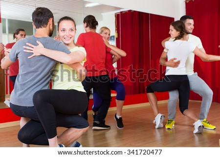 smiling men and women  dancing bachata together in dance studio - stock photo