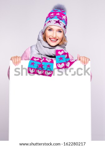 Smiling  woman in winter outerwear holds the white banner in hands at studio - stock photo