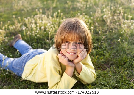 Smiling young boy lying on grass - stock photo