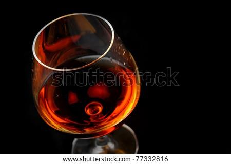 snifter of  brandy in  elegant  glass.  black background - stock photo