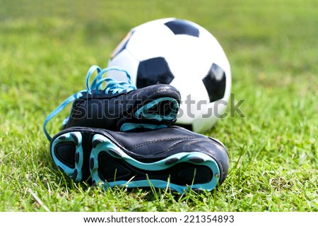 soccer ball and shoes in grass - stock photo
