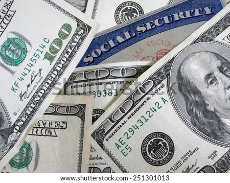 social security card buried in one hundred dollar bills   - stock photo