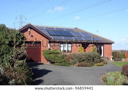 16 Solar Panels on Bungalow Roof in UK including power lines - stock photo
