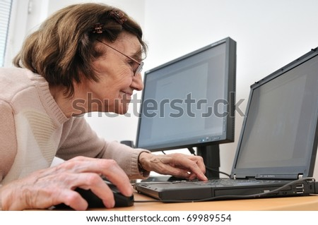 80-something senior woman working with laptop, another computer in the background - stock photo