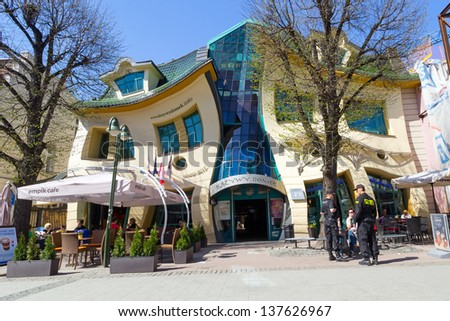 SOPOT, POLAND  -  MAY 06.2013:  The Crooked house on the main street of Monte Cassino in Sopot, Poland.The Crooked House is an irregularly-shaped building.1 of  50 strangest buildings of the world. - stock photo