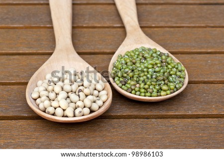 Soy beans and green beans on teak table - stock photo