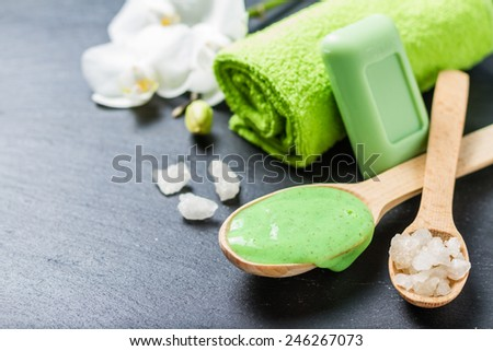 SPA and wellness - towel, orchid flower, salt, soap and body scrub on dark stone background - stock photo
