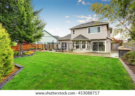 Spacious backyard garden of large beige house with green lawn and Cozy patio area.  - stock photo