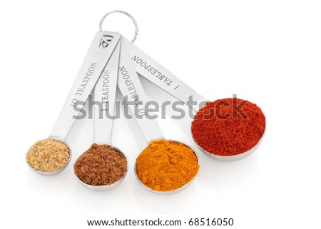 Spice selection of paprika, turmeric, chinese five spice and  ginger in stainless steel measuring spoons, over white background. Right to left. - stock photo