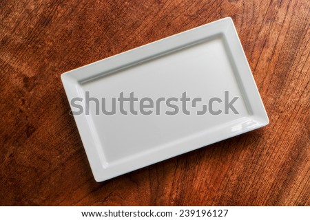 square plate on the wood background. - stock photo